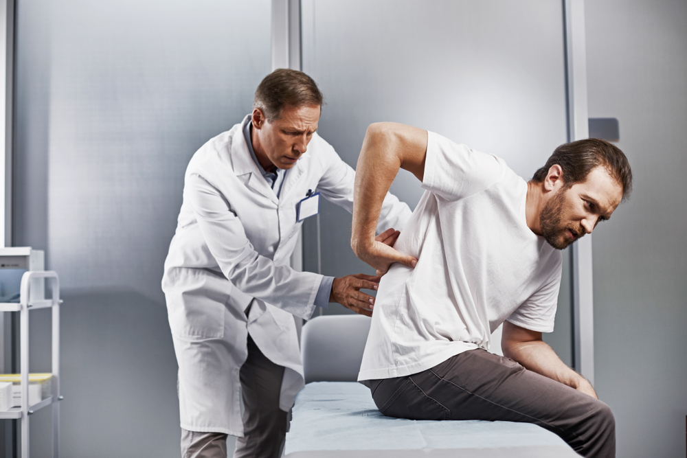 Doctor Performing an Epidural steroid injection on male patient